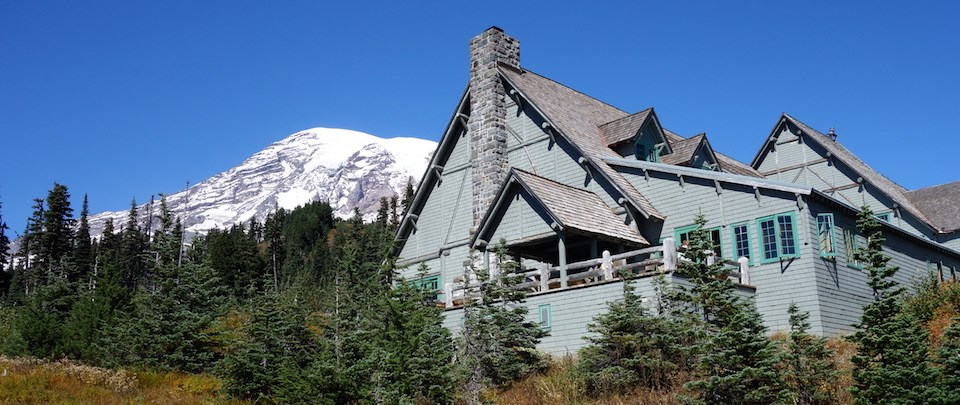 A large wood building with pitched roofs and a deck in front of Mount Rainier.