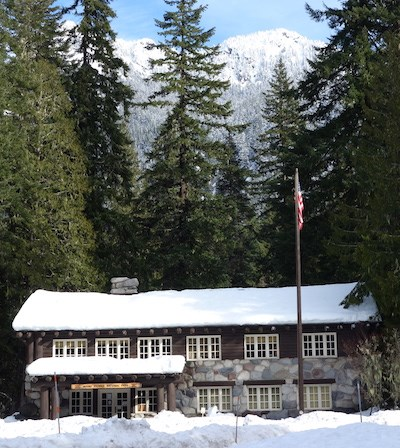 Rustic building with snow covered roof framed by conifer trees.