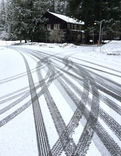 Tire tracks crisscross on a snowy road.