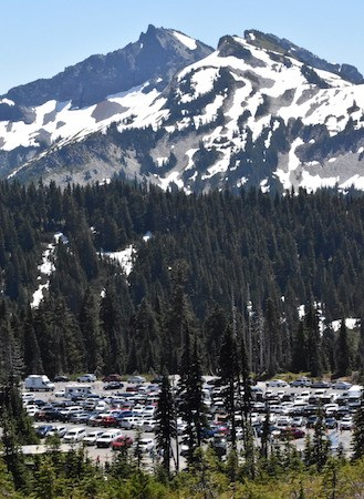 A full parking lot beneath forested slopes and rocky peaks.