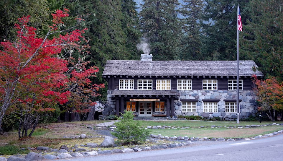 A two-story wood and stone building surrounded by forest and red vine maple trees.