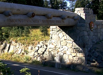 The large logs of the Chinook Entrance Arch stretch over the road, inset into rock foundations.