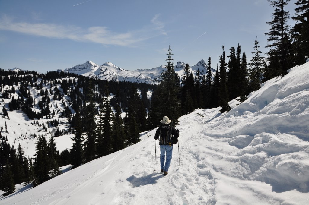 A hiker walks along a snowy trail in the mountains.