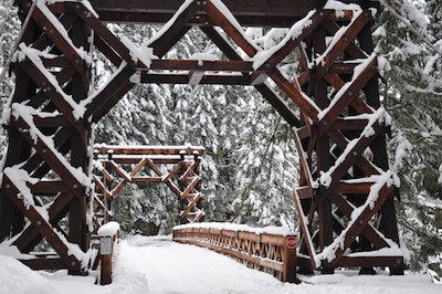 Wooden suspension bridge dusted with snow.