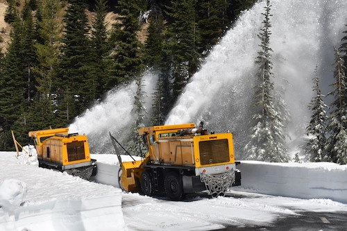 Two yellow rotary snow blowers shooting plumes of snow into the trees from a snow-covered road.