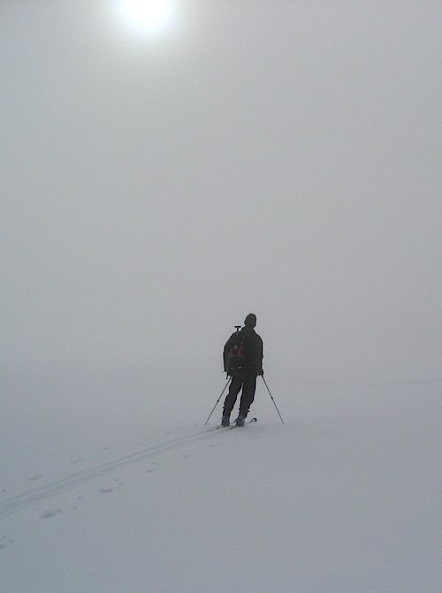 A skier pauses on a snowy slope as fog obscures the landscape.
