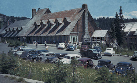 Historic colored photo of a wood and stone building with 1940s-era cars parked in front.