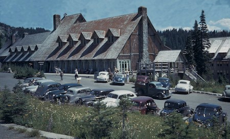 Historic Colored Photo Of A Wood And Stone Building With 1940s Era Cars Parked In