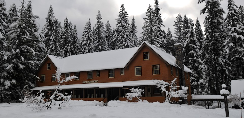 A wood building with pitched roofs covered in snow in a snowy forest.