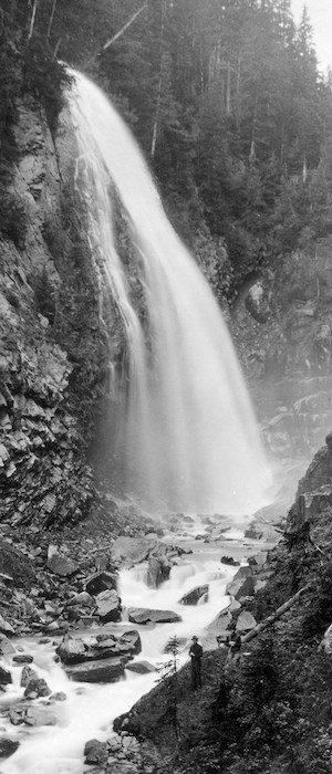 A black and white historic photo of a waterfall with a man standing at its base.