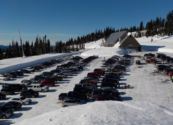 Cars fill a parking lot in front of a building with a steep roof and surrounded by deep snow banks on a sunny day.