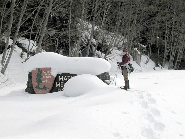 Volunteer snowshoeing at Mather Memorial Sign