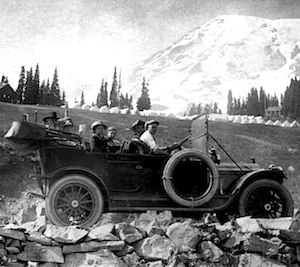 Visitors sit in an open-top old car in front of Mount Rainier in a black and white photo.