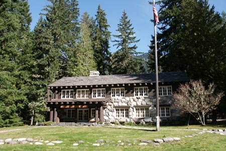 A historic wood and stone structure stands before tall evergreens and blue sky.