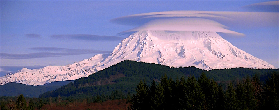 Lenticular, disc-shaped, clouds cling to the peak of Mount Rainier.