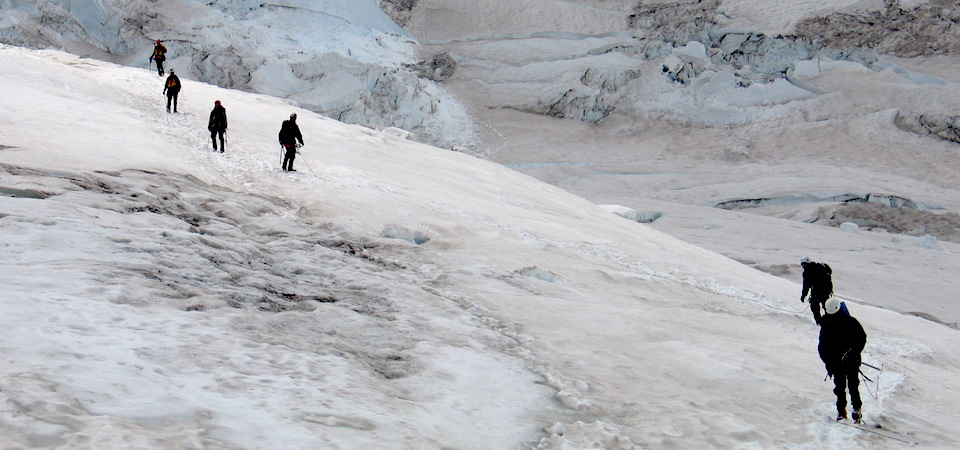 A string of climbers cross a glacier.