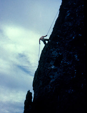 A climber braces against a rope as he ascends a steep cliff.