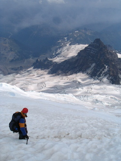 A climber looks down the Emmons glacier towards Disappointment Cleaver.