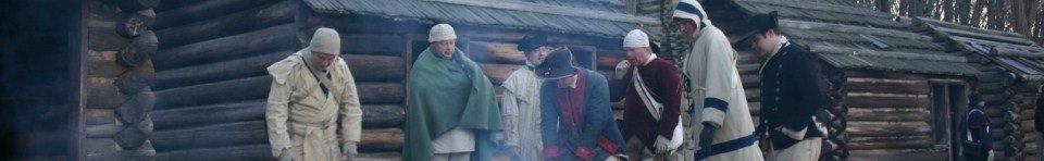 Reenactors try to stay warm outside soldier huts in Jockey Hollow
