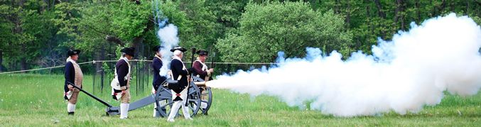 A cannon is fired by 5 men dressed as Continental soldiers, with a billow of smoke coming from the mouth of the cannon.