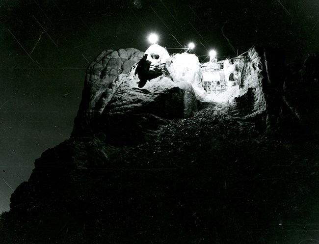 Black and white photograph of an attempt in 1939 to illuminate Mount Rushmore from the top of the sculpture.