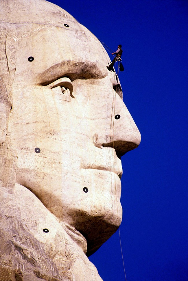 A worker installs scanning targets on George Washington's face on Mount Rushmore.