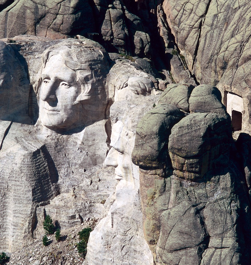 Photo of the location of the Hall of Records across a small valley behind the sculpted heads on Mount Rushmore.