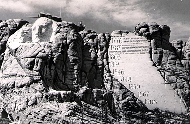Photo of Mount Rushmore as carving began with conceptual drawing of Borglum's idea for an entablature.