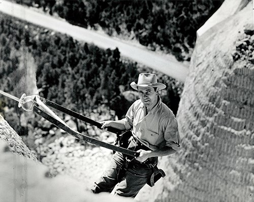 Lincoln Borglum in a bosun chair on the side of Mount Rushmore.