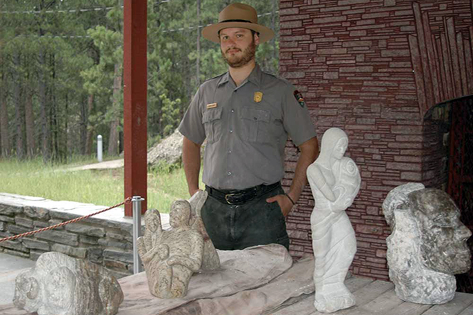 Artist in Residence Dustin Baker with some of his sculptures at Mount Rushmore.