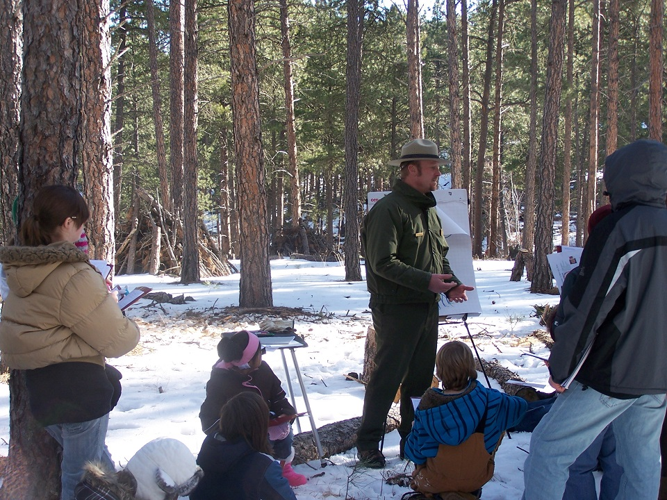 Mount Rushmore Interpretive Park Ranger Blaine Kortemeyer teaches Project Citizen students about the effects of the mountain pine beetle on the ponderosa pine forest.