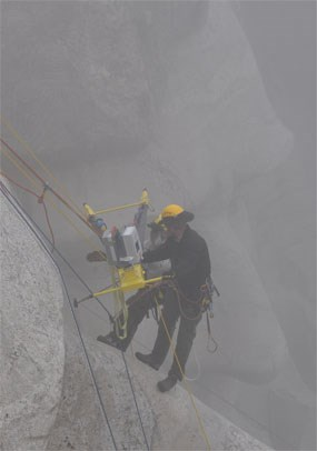 Two members of the Mount Rushmore technical ropes team work through the fog to position the custom made tripod on Thomas Jefferson's nose.