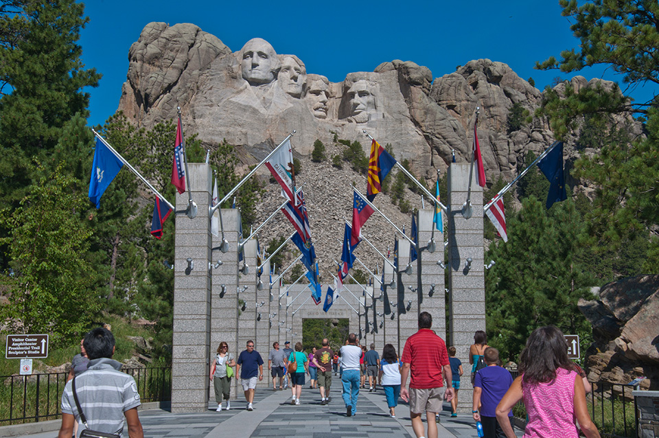 Visitors walk along the Avenue of Flags with Mount Rushmore in the background.