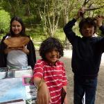 Photo of three kids holding a piece of redwood, a banana slug, and deer antlers