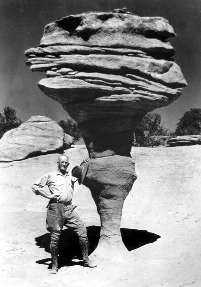 historical black and white photo of a man leaning against a large rock formation precariously perched on a spindly base