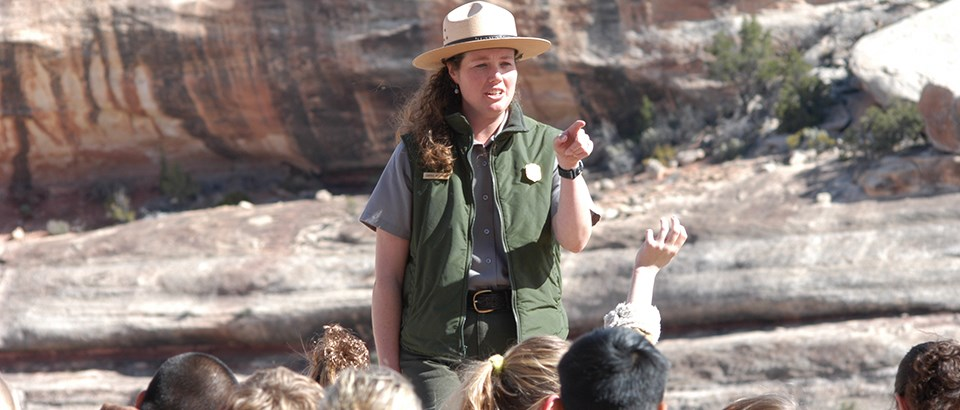 a park ranger points while children in the foreground raise their hands