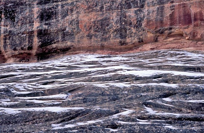 blue-gray sandstone with crossbedding, or hash scores, outlined with melting snow and red sandstone in the background