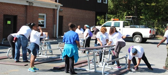 a picture of volunteers putting together picnic tables