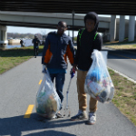 Young volunteers hold bags of litter they collected