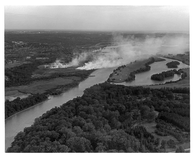 An aerial black and white photo shows smoke wafting from the landfill across the Anacostia River and over the Langston golf course.