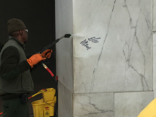 NPS employee removes graffiti at Lincoln Memorial