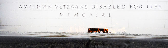 American Veterans Disabled for life Memorial words on white wall; eternal flame and pool in front