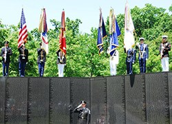 US Park Police officer salutes in front of Honor Guard at The Wall