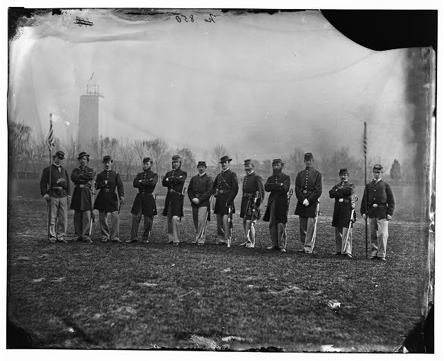 Union soldiers standing in a row in front of the unfinished Washington Monument