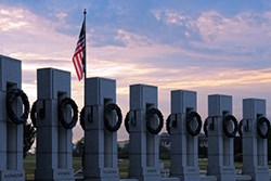 sunrise in front of pillars and flag