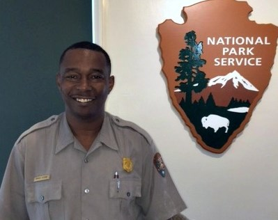 Smiling man wearing grey shirt with NPS badge over right pocket and NPS arrowhead on right sleeve