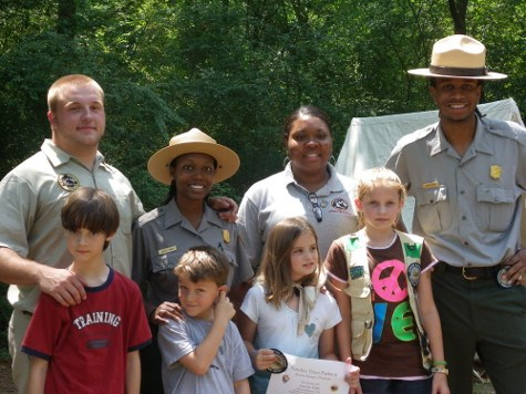 a group of park rangers, volunteers, and new junior rangers pose for the camera