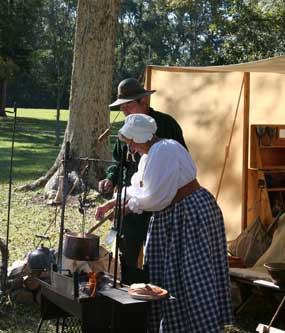 Visitors talk with members of the Tombigbee Pioneer Group at their encampment.