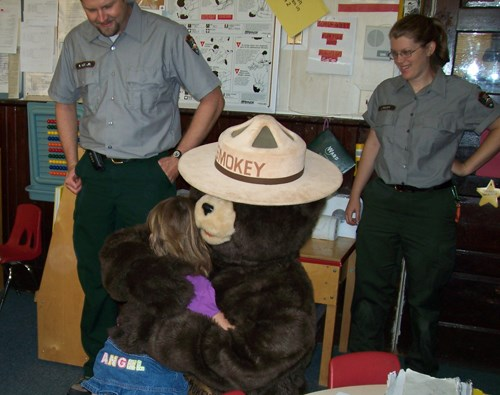 Smokey Bear greets a student in her classroom.