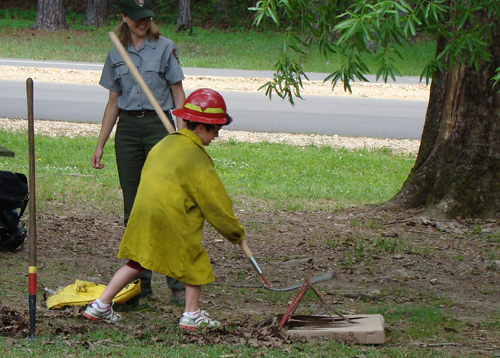 "A young visitor puts out ""flames"" while wearing some of the proper safety clothing."